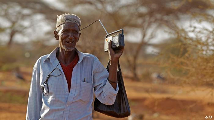 A man holds a radio in his hand