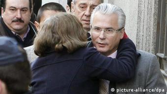 Woman embraces Baltasar Garzon as he enters court