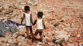 Two children hold hands and walk in the rubble of a slum Photo: (AP) Mustafa Quraishi,