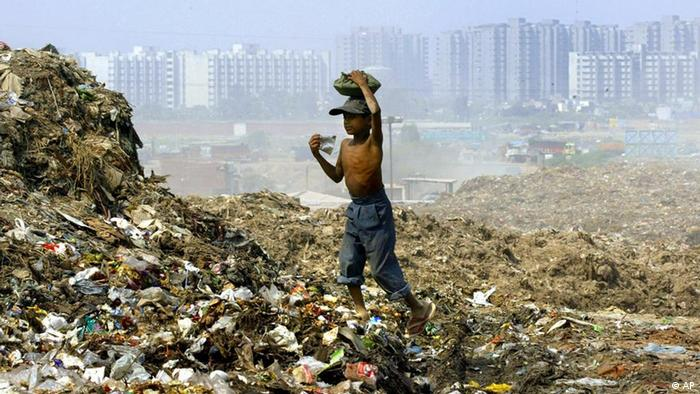 A boy, who refused to be identified, carries food to his family working at a garbage dump near a residential colony in New Delhi