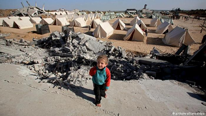 Palestinian boy walks in a tent area erected in the east of Jabaliya refugee camp in the northern Gaza Strip
