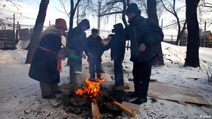 Homeless people stand around a fire warming up as they wait for a free dinner provided by the Russian Orthodox church near a railway terminal in Moscow, Wednesday, Feb. 1, 2012. In Moscow temperatures fell to minus 21 C (minus 6 F). (Foto:Alexander Zemlianichenko/AP/dapd)