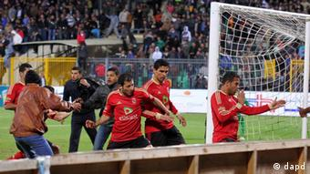 Team players of the Egyptian Al-Ahly club run for safety