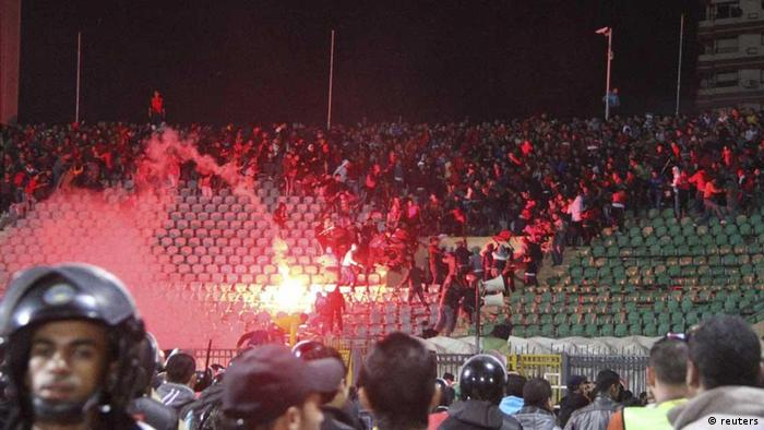 Soccer fans flee from a fire at Port Said Stadium