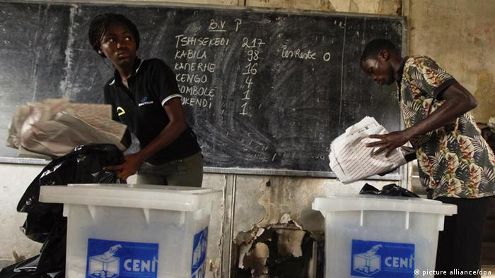 Kinshasa 2011: electoral agents remove counted ballot papers from the boxes as initial results are shown on a blackboard behind them.