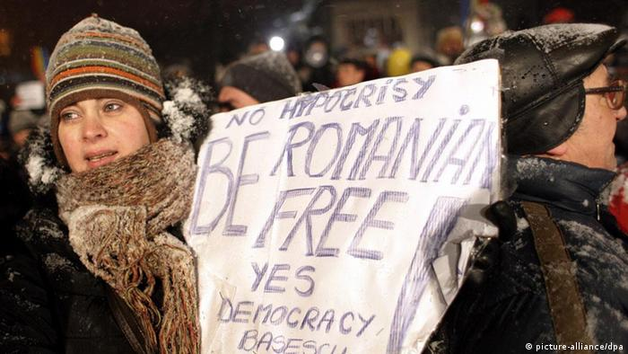 A Romanian woman holds a placard while facing a strong blizzard during a protest at University Plaza in Bucharest, Romania, 25 January 2012. Demonstrators from all over the country demanded the government to resign and asked for anticipate elections, joining the nation-wide spread protests which entered into the thirteenth consecutive day. Romanian Prime Minister Emil Boc announced on 23 January that he fired the foreign minister, Teodor Baconschi, due to the insulting remarks he made about anti-government protesters. EPA/ROBERT GHEMENT +++(c) dpa - Bildfunk+++ Schlagworte CITIZENS INITIATIVE & RECALL, CITIZENS INITIATIVE &