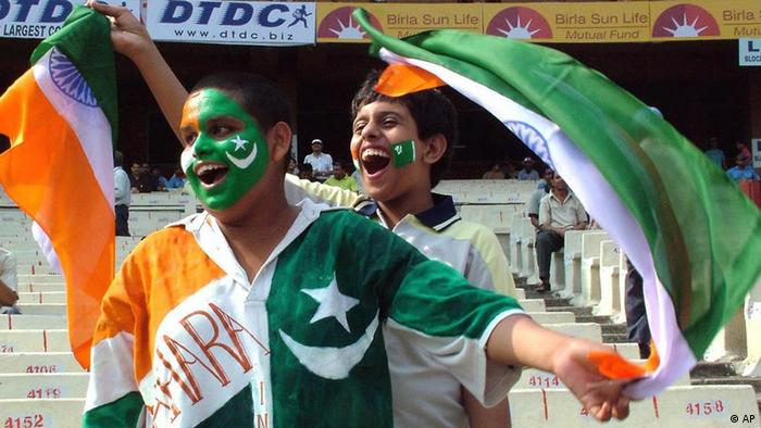Cricket fans, their faces painted with the Indian and Pakistani national flags, cheer during the first day of the second cricket test match between India and Pakistan at the Eden Gardens in Calcutta, India, Wednesday, March 16, 2005 (Photo: AP)