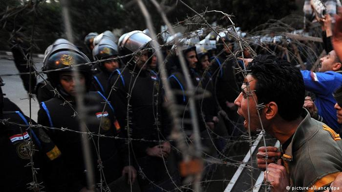 Egyptian protesters face security soldiers and shout slogans