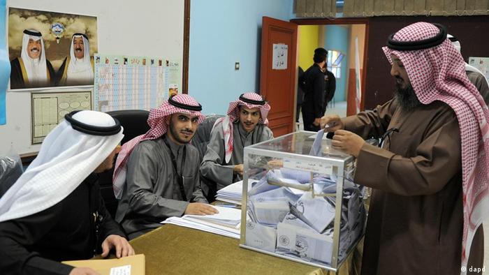 A Kuwaiti citizen casts his vote at a polling station