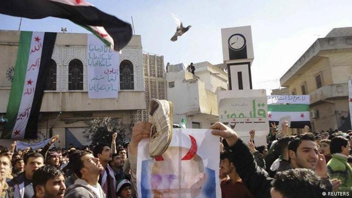 Demonstrators hold a vandalized poster of Russian Prime Minister Vladimir Putin as they take part in a protest against Syria's President Bashar al-Assad after Friday prayers in Talbiseh.