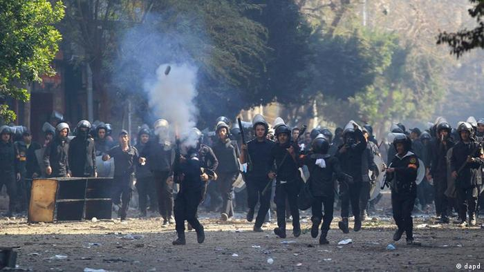 Egyptian security forces fire tear gas at protesters during clashes near the Interior Ministry in Cairo