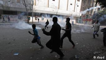 Egyptian protestors run for cover from tear gas fired by security forces during clashes near the Interior Ministry in Cairo, Egypt, Saturday, Feb. 4, 2012. The number of people killed in clashes with Egyptian security forces in the wake of a deadly soccer riot rose on Saturday, according to a field doctor and a security official, as demonstrators in Cairo kept up their calls for an end to military rule and retribution for those killed in the soccer game violence. (Foto:Khalil Hamra/AP/dapd)