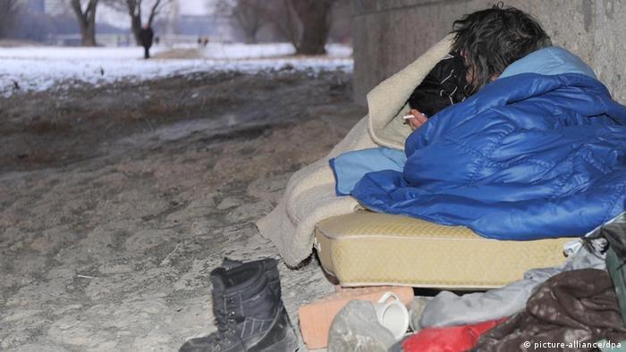 Ein Obdachloser schläft im Schnee