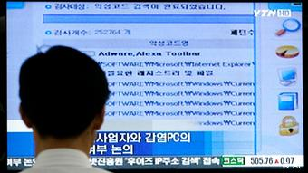 Ein Mann sitzt vor einem großen Bildschirm (Foto: AP)