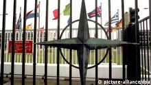 Der Nato-Stern und wehende Flaggen der Mitgliedsstaaten vor dem Gebäude des Nato-Hauptquartiers im belgischen Brüssel (Archivbild vom 5.9.1995)