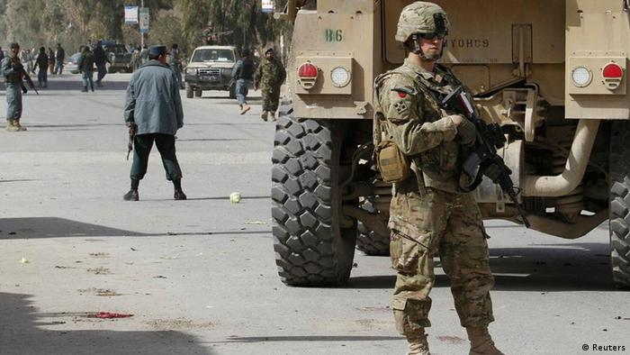 A U.S. soldier keeps watch near the site of a car bomb blast in the city of Kandahar February 5, 2012. The car bomb in the south Afghan city of Kandahar killed at least seven people and wounded 19 on Sunday, the province's media office said. REUTERS/Ahmad Nadeem (AFGHANISTAN - Tags: CIVIL UNREST)
