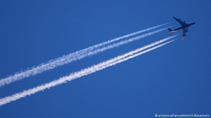 Flugzeug mit Kondensstreifen an einem blauen Himmel.