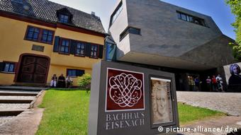 An old building next to a new one with Bach's outdoor pictures and a sign with Bach House Eisenach (picture-alliance / dpa)