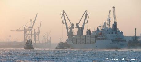 Ein Containerschiff, begleitet von Schleppern, fährt am Montag (06.02.2012) bei Sonnenaufgang durch die vereiste Elbe im Hamburger Hafen. In Norddeutschland hat sich die eisige Kälte festgesetzt. Die Elbe ist bereits seit Freitag teilweise für den Schiffsverkehr unbefahrbar. Foto: Christian Charisius dpa/lno