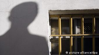 ARCHIV - Der Schatten eines Mannes ist am 07.11.2009 neben einem Gitterfenster des ehemaligen Geschlossenen Jugendwerkhofes Torgau in der heutigen Gedenkstätte in Torgau (Sachsen) zu sehen. Auch in staatlichen Heimen der DDR hat es Fälle von Gewalt und sexuellem Missbrauch an Kindern und Jugendlichen gegeben haben. Bei der Leiterin der Gedenkstätte melden sich mehr und mehr ehemalige Insassen von DDR-Kinderheimen, die von massiven Übergriffen ihrer Erzieher berichten. Foto: Peter Endig dpa/lsn (zu lsn Korr.-Bericht Besuch in Torgau: Wenn Du nicht brav bist ... am 05.04.2010) +++(c) dpa - Bildfunk+++
