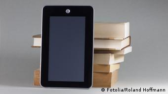 E-book next to stack of paper books