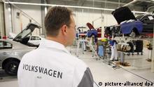 Ein Mitarbeiter von Volkswagen RUS blickt am Montag (25.08.2008) im Volkswagen-Werk im russischen Kaluga in einer Werkshalle auf die Produktion von Fahrzeugen. Die deutschen Autobauer erwarten in diesem Jahr auf dem boomenden Automarkt Russland ein enormes Wachstum. Während der Gesamtmarkt 2008 voraussichtlich um ein Viertel auf 3,1 Millionen Einheiten steige, werde der Absatz deutscher Pkw-Modelle um rund ein Drittel auf 465000 Einheiten zunehmen, teilte der Verband der Automobilindustrie am Dienstag anlässlich der Automesse in Moskau mit. Foto: Friso Gentsch +++(c) dpa - Report+++