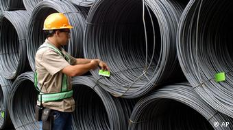 In this May 2004 photo provided by French steelmaker Arcelor SA, a worker checks wire rod rolls at the Belgo Juiz de Fora production plant, in Brazil. Mittal Steel Co. announced Friday Jan. 27, 2006 a surprise $22.8 billion offer for rival Arcelor SA , a deal that would unite the world's largest steelmaker with its closest rival to create a global powerhouse capable of producing more than 100 million tons a year. (AP Photo/P F Grosjean, Arcelor)
