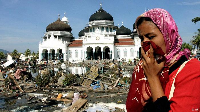 A woman walks near a mosque with the rubbish from the quake and tsunami in Banda Aceh Tuesday, Dec. 28, 2004. The Health Ministry said in a statement early Wednesday that 27,178 people have been killed on Indonesia's Sumatra Island.. (AP Photo/str)