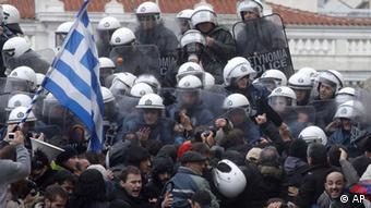 Riot Police push back protestors, one waving the Greek flag, who try to enter at the Parliament building at Athens' main Syntagma square, during a 24-hour strike on Tuesday, Feb. 7, 2012. A general strike against the impending cutbacks stopped train and ferry services nationwide, while many schools and banks were closed and state hospitals worked on skeleton staff. (Foto:Petros Giannakouris/AP/dapd)