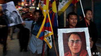 Exile Tibetans hold portraits of spiritual leader the Dalai Lama, right, and 21-year-old monk Phuntsog and participate in a candlelit vigil to honor the monk who set himself on fire in an anti-government protest, in Dharmsala, India, Thursday, March 17, 2011. (AP Photo/Ashwini Bhatia)