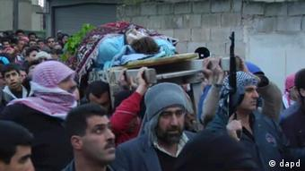 This image taken from video filmed over the past several days by an independent cameraman and made available Tuesday Feb. 7, 2012 shows a dead man carried outside in a funeral procession in Homs, Syria. The bombardment of Homs, the hot bed of the resistance to President Bashar Assad's regime, has intensified over recent days, after Syria's allies Russia and China vetoed a Western and Arab-backed resolution at the United Nations that would have condemned the Assad regime's crackdown on dissent and called on him to transfer some of his powers to his deputy. (Foto:APTN/AP/dapd)