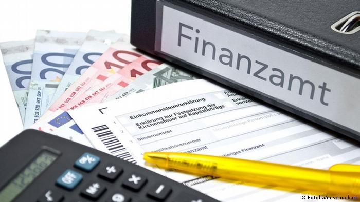 Geldscheine, ein Aktenordner, ein Taschenrechner und ein Formular für die Einkommensteuererklärung.