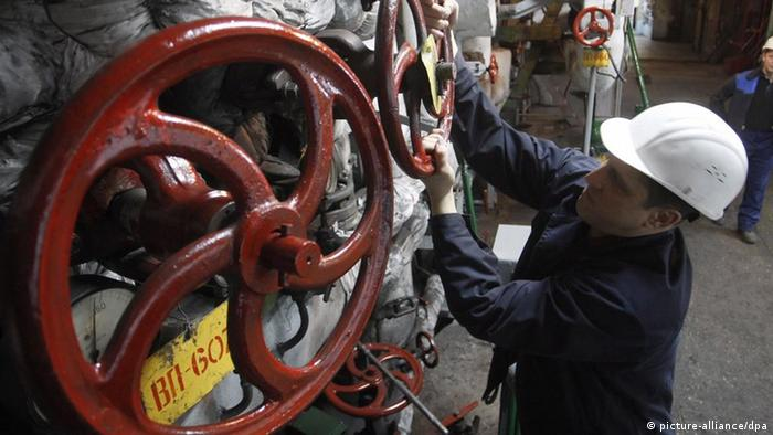A Ukrainian worker opens a valve at a city heating and electro-power station