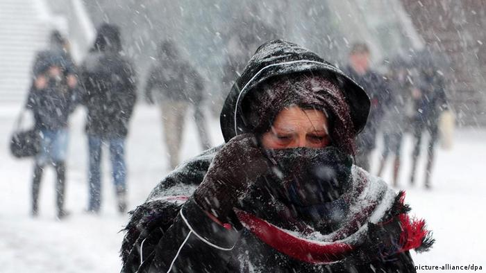 A woman has wrapped herself into her coat and scarf as she walk during snowfall in Skopje