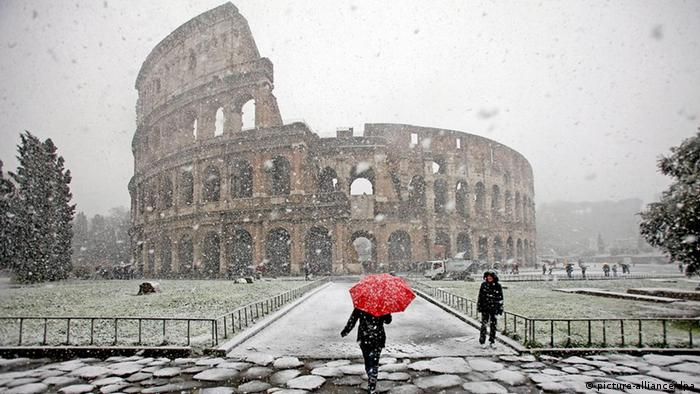 The Colosseum is partly obscured by falling snow