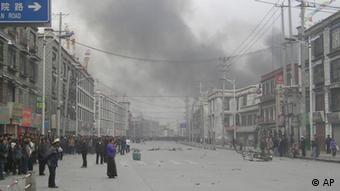 Smoke billows from behind buildings after Tibetans rioted in Lhasa in 2008