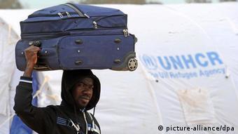 Ein Flüchtling trägt seinen Koffer (Bild: picture-alliance/dpa)