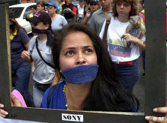 Mayra Linares, with her mouth covered and holding a mock television screen, marches to protest against a new media law which the opposition believes will threaten press freedom, in Caracas, Venezuela, Saturday, Dec. 4, 2004.