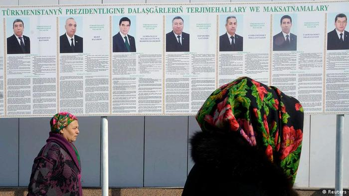 Women walk past a board displaying portraits of presidential candidates in the Turkmen capital Ashgabat