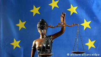 Statue of blindfolded Justitia holding balanced scales with the EU's flag in the background Photo: Peter Endig +++(c) dpa - Report+++