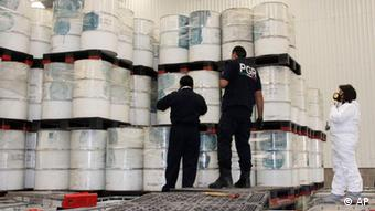 Mexican police investigators look at drums of precursor chemicals for methamphetamine that were seized in Queretaro, Mexico