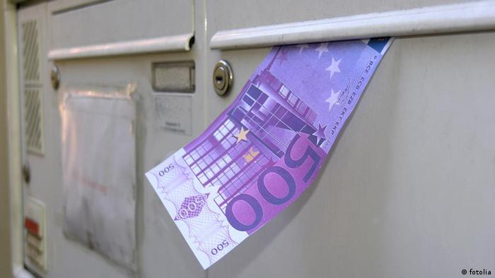 Euro banknote in the slot of a mailbox