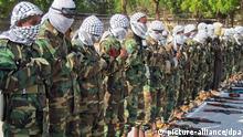 Vermummte Mitglieder der Al-Schabaab-Miliz in Somalia haben am 16.11.2010 in Mogadischu während eines Gebets ihre Gewehre abgelegt. Die islamistische Al-Schabaab-Miliz wurde 1998 in Somalia gegründet und hat Verbindungen zum Terrornetzwerk Al-Kaida. Die Miliz beherrscht weite Teile Südsomalias und damit die Gebiete, in denen die derzeitige Hungersnot am schlimmsten ist. Foto: Badri Media (zu dpa-Hintergrund 0330 vom 07.08.2011) +++(c) dpa - Bildfunk+++
