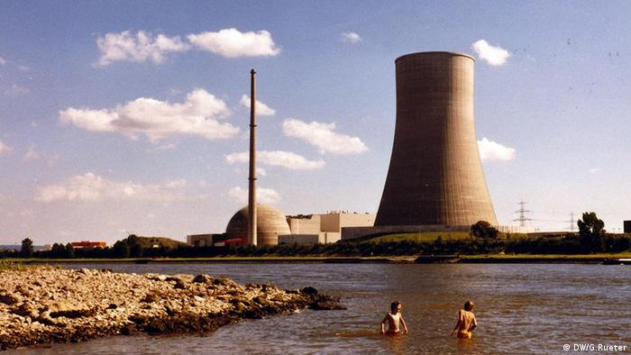 Two people in a river with the nuclear power plant Mülheim-Kärlich in the background