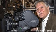 Michael Ballhaus steht im Filmmuseum von Berlin neben einer 35mm-Filmkamera (Archivfoto vom 22.11.2001). Der Kameramann wird am Freitag (05.08.2005) 70 Jahre alt. Ein Star hinter der Kamera war Ballhaus schon in den 70er Jahren in Deutschland, wo er mit Rainer Werner Fassbinder 15 Filme drehte. Seine entfesselte Kamera prägte den Neuen Deutschen Film. Markenzeichen des Ballhaus-Looks sind flüssig-elegante Fahrten, exquisites, sattes Licht und die berühmten kreisenden Kamerabewegungen rund um die Darsteller. Seiner Leidenschaft für Bilder und Theater, die er schon als junger Bühnenfotograf in Berlin entdeckte, schreibt er seinen Erfolg zu. Foto: Bernd Settnik dpa (zu dpa-Korr.: Ein Star hinter der Kamera - Michael Ballhaus wird 70 Jahre vom 31.07.2005) +++(c) dpa - Report+++ Schlagworte Film, Kultur, Medien, Personen, Arri, Filmkamera, kameramann, lächeln