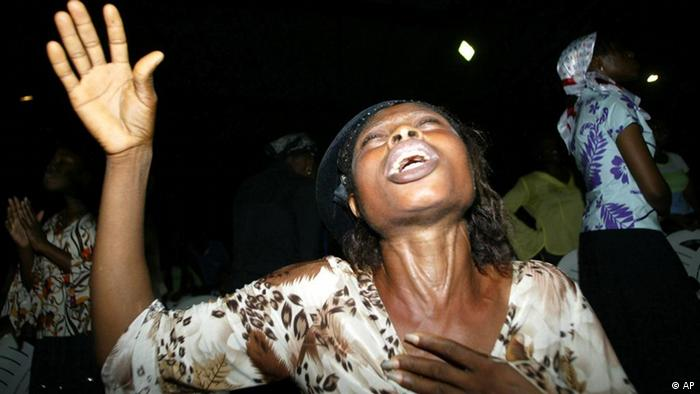 A woman lifts her hand and shouts out in rapture at the Redeemed Christian Church of God in Lagos, Nigeria