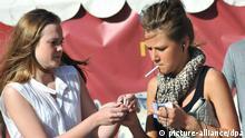 Young women smoke near the entrance to Ohotny Ryad metro stop on Tverskaya Street. pixel