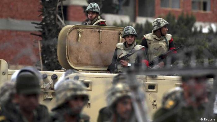 Egyptian soldiers stand guard near the defence ministry during a protest demanding that the army hand power over to civilians in Cairo February 10, 2012