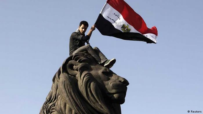 Demonstran membawa bendera Mesir ke Lapangan Tahrir.