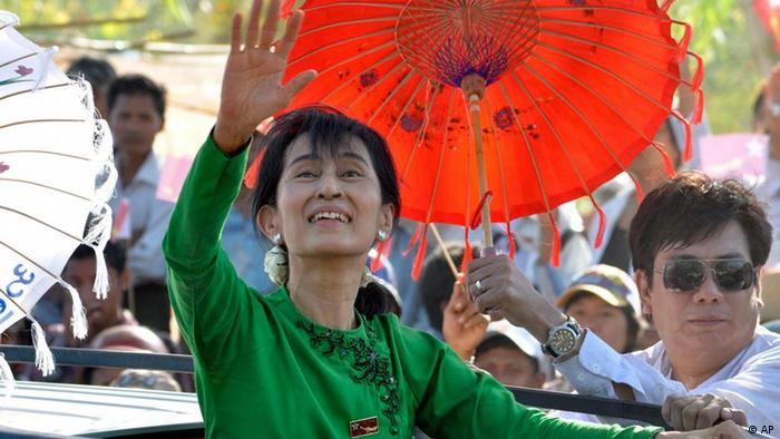 In this photo taken Tuesday, Feb.7, 2012, Myanmar pro-democracy icon Aung San Suu Kyi greets supporters as she arrives at Myaung-Mya, the Irrawaddy Delta, Myanmar. Crowds of supporters greeted Myanmar opposition leader Aung San Suu Kyi with thunderous applause as she embarked Tuesday on her first campaign trip since becoming an official candidate for April elections. (AP Photo/Khin Maung Win)